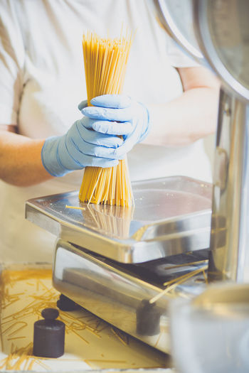 Midsection of woman packing spaghetti in factory
