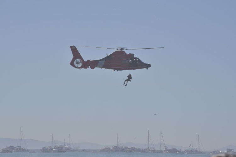 Sky Flying Mode Of Transportation Transportation Mid-air Nature Motion Clear Sky Day Outdoors Helicopter US Coast Guard US Coast Guard Rescue Swimmer And HH65 Helicopter. Rotor Wash Low Flying Aircraft Diver Rescue Rescue Swimmer Ocean Sea Boats Propeller Rotor Blue Sky Full Frame Shot