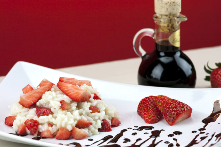 Close-up of dessert with strawberries served in plate and drink on table against red background