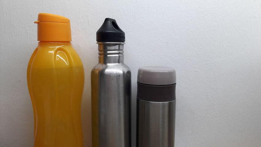 BottleArranging In Order Orange Silver Metallic Bottle White Background Table Loyal Green Tupperware Haers