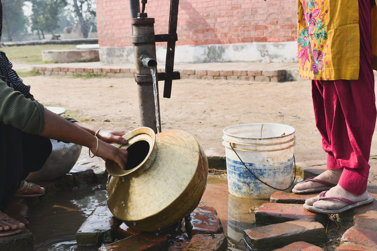 Low section of woman washing water pot