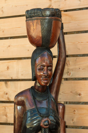 Close-up of statue by wooden wall