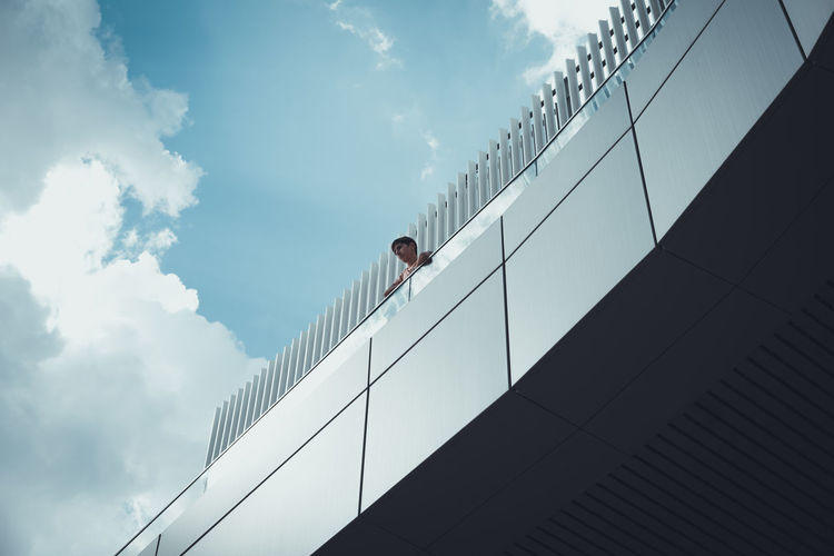 Low angle view of man looking away while standing in balcony against sky