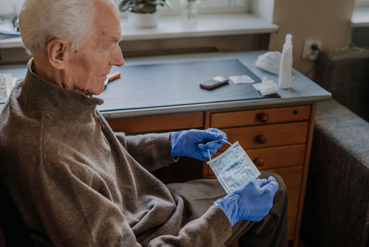 Senior man holding surgical mask at home