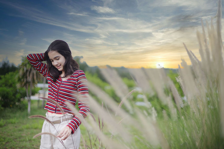 Young woman standing on field against sky during sunset