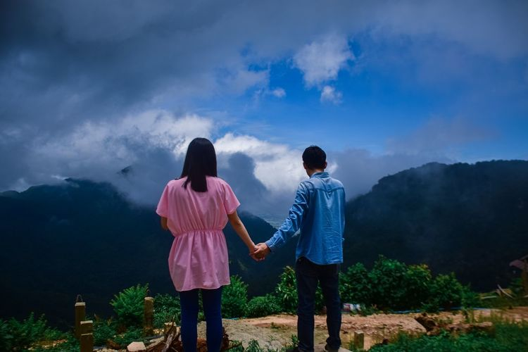 Rear view of couple holding hands standing on mountain against sky