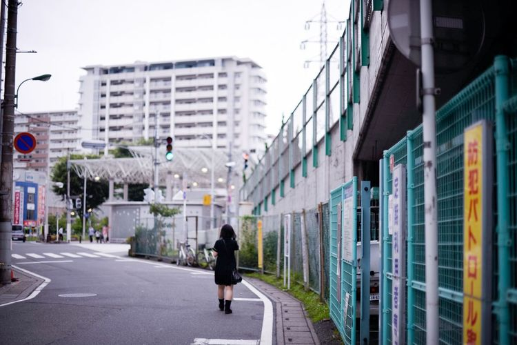 Rear View Of Woman Walking On Road By Fence Leading Towards Buildings