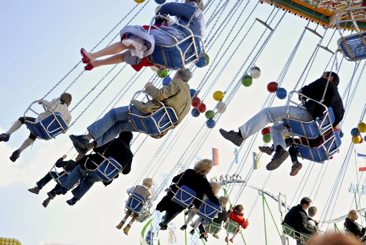 Low angle view of people on chain swing against sky
