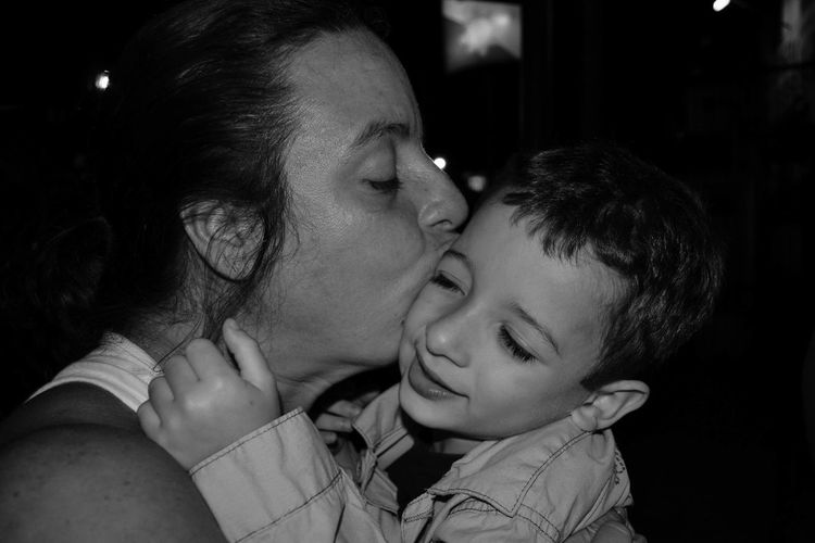 Close-Up Of Mother Kissing Son At Home