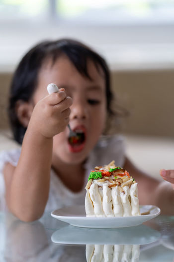 Close-up of girl eating cake at home