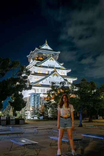 Portrait of woman standing at illuminated temple against sky at night