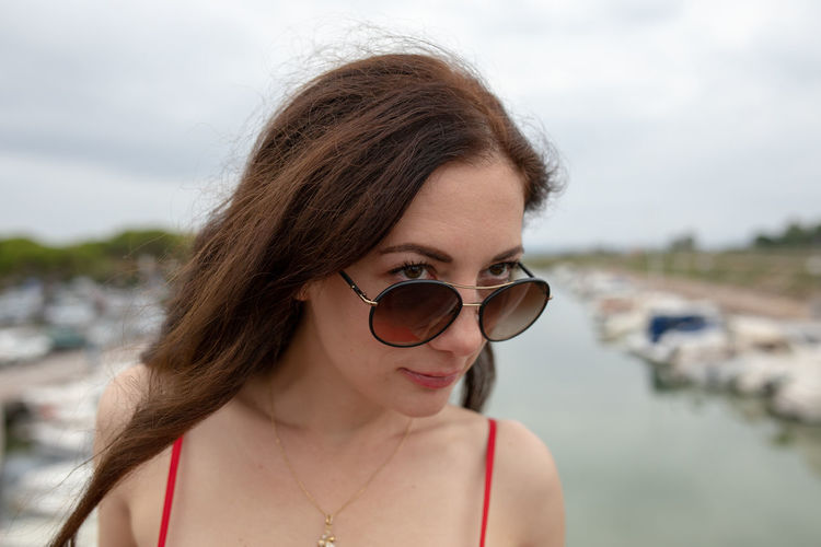 Close-up of thoughtful woman wearing sunglasses while standing against harbor