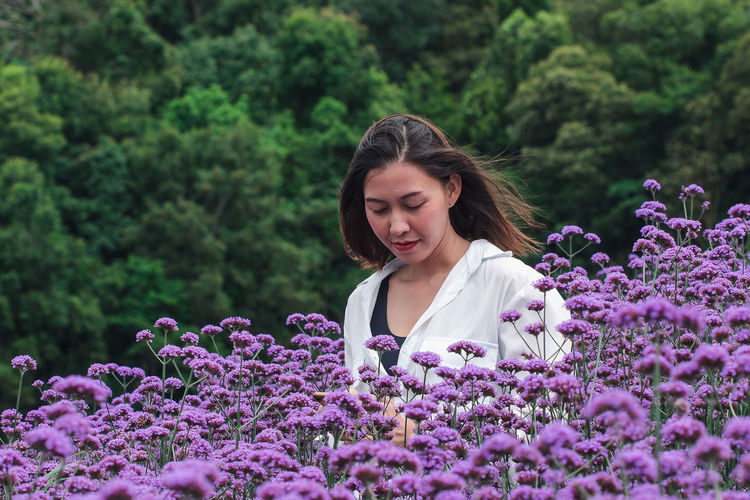 Young woman with purple flowering plants