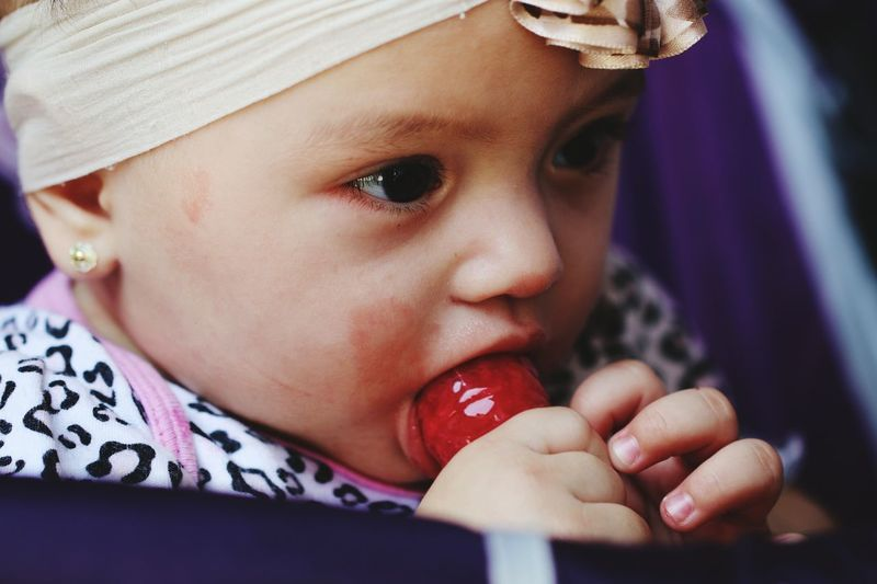 Close-Up Portrait Of Baby With Lollipop