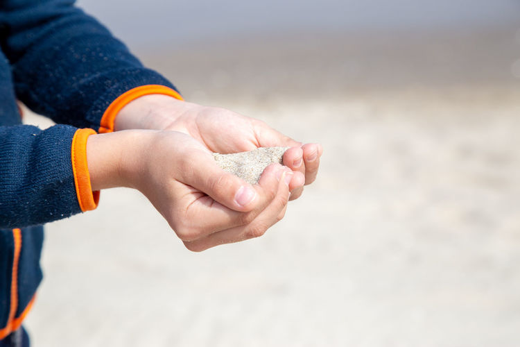Midsection of child holding hands on beach
