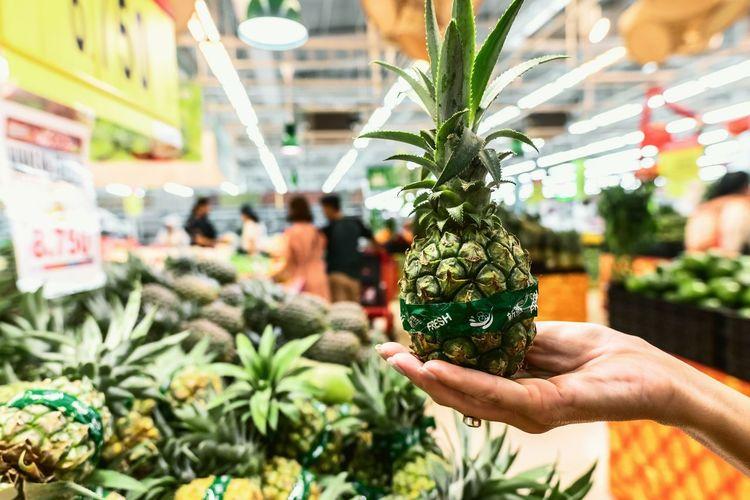 Hand holding vegetables at market stall