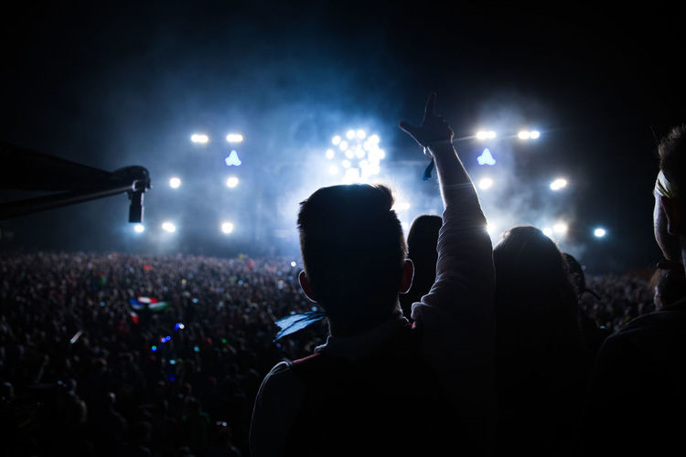 Rear view man gesturing towards crowd during music concert