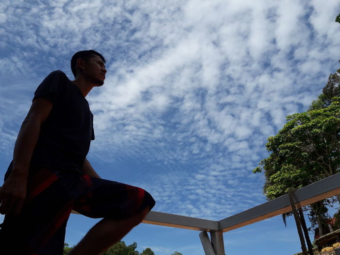 Low angle view of man looking away against sky