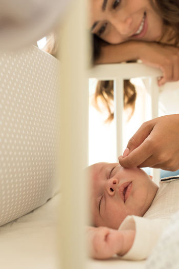 Mother touching toddler son sleeping in crib at home