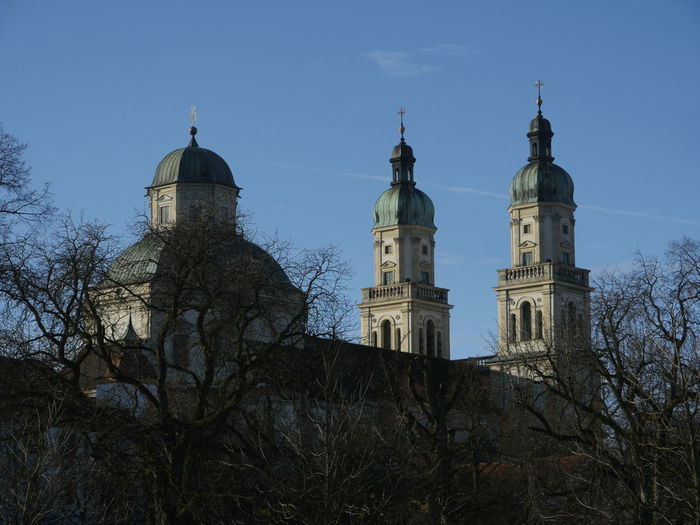 Low angle view of bare trees by st lorenz basilica against blue sky