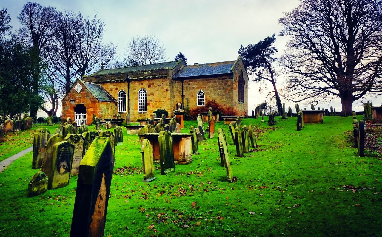 cemetery, tombstone, bare tree, sky, grass, outdoors, day, tree, no people, green color, architecture, built structure, cross, graveyard, building exterior, nature