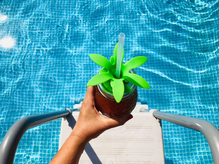 Cropped hand of woman holding drink over swimming pool