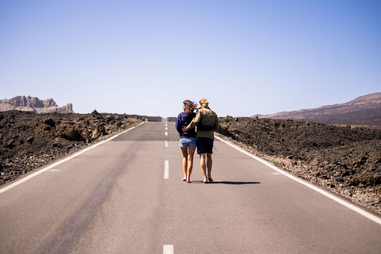 nice young couple viewed from rear walking together hugging on a long way road in the middle of the lava desert on an asphalt road. clear sky in background and arid landscape around them. love and friendship concept National Park Walking Around Adult barefoot Clear Sky Desert Landscape Diminishing Perspective Direction Full Length Leisure Activity Lifestyles Mountain Nature Outdoors People Real People Rear View Road Sky Sunlight The Way Forward Togetherness Transportation Two People Women