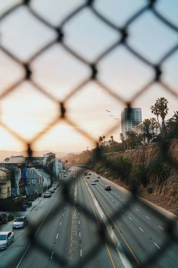 Cars On Highway Seen Through Chainlink Fence