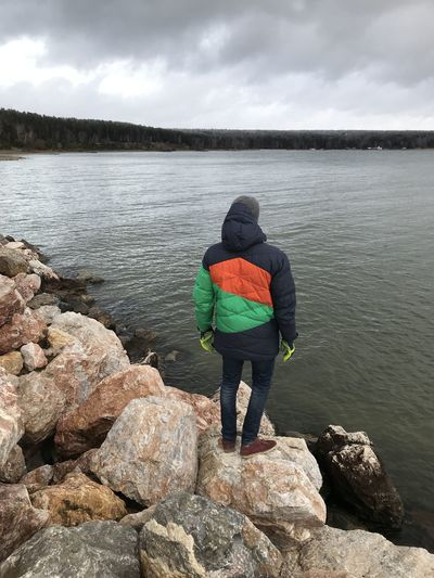 Rear view of man standing on rock by lake against sky