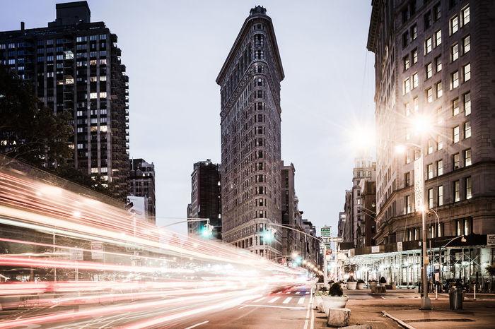 Light trails on urban street against buildings