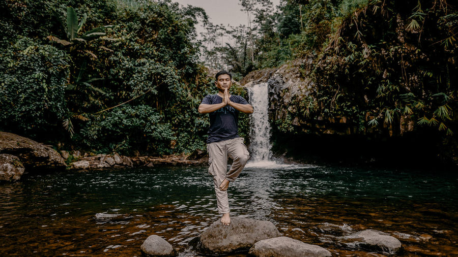 man standing by water fall and plants in forest