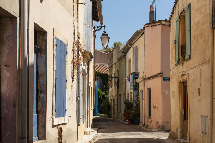 A narrow street at Arles, France Alley Architecture Blue Building Exterior Built Structure Day Diminishing Perspective Empty Footpath Greenery In A Row Leading Long Narrow No People Old Town Outdoors Residential Structure The Past The Way Forward Tourism Town Travel Destinations Window