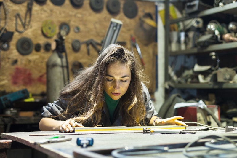 young woman working in a workshop Industry Measuring Messy Service Worker Working Workshop Art And Craft Concentration Dedicated Equipment Front View Garage Headshot Indoors  Long Hair Looking Down Occupation One Person Portrait Repair Table Technician Tools Women