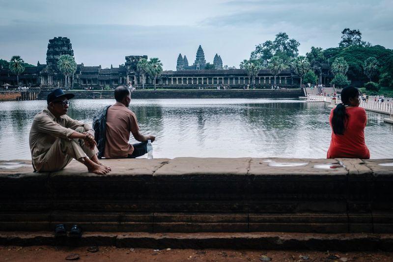 Men sitting on riverbank against sky
