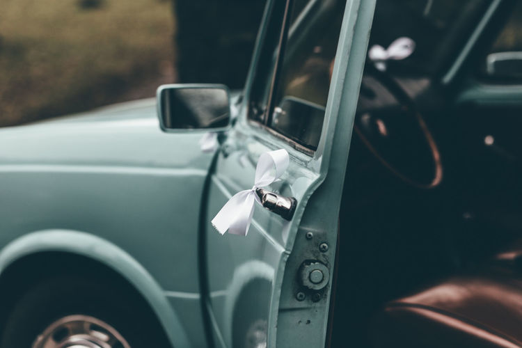 Blue Vintage Car Car Car Interior Close-up Day Land Vehicle Mode Of Transport No People Outdoors Reflection Side-view Mirror Transportation Vehicle Interior Vehicle Mirror Vintage Car Vintage Wedding Car Wedding Car Wedding Ribbons White Ribbons Windshield