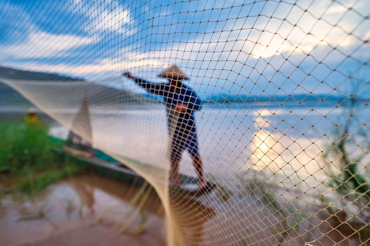 In the early morning before sunrise, an asian fisherman on a wooden boat casts a net for catching
