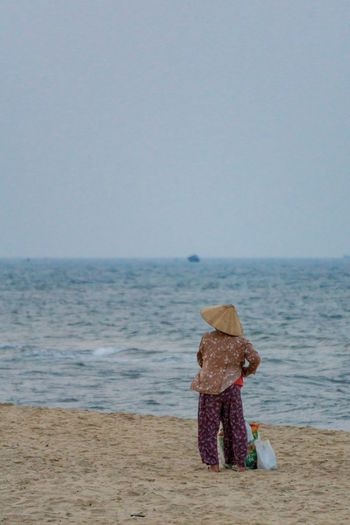 Vietnamese grandmother with the sea. Asian  Loneliness Lonely Tranquility Vietnam Asian Style Conical Hat Beach Beauty In Nature Clear Sky Countryside Hat Horizon Horizon Over Water Nature Outdoors People Rear View Rural Scene Sand Scenics - Nature Sea Sky Tranquil Scene Water Women
