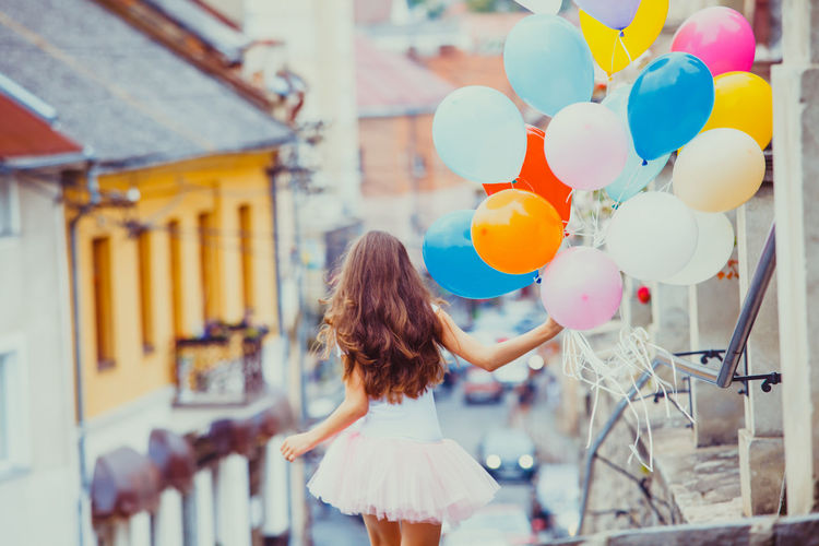 Rear view of teenage girl holding balloons outdoors