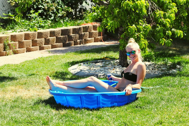 Side View Of Woman In Wading Pool On Field