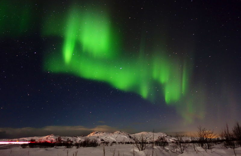 Scenic view of landscape against sky at night during winter