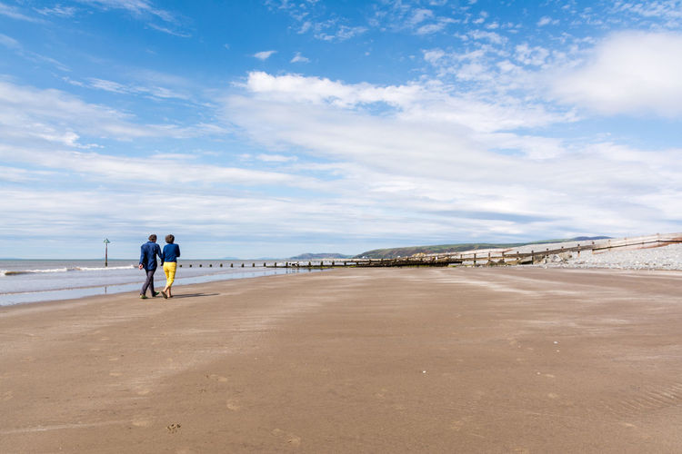 Rear view of couple walking at ynyslas beach against sky