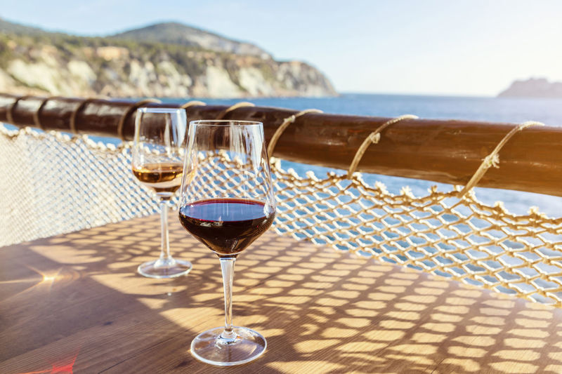 Wine glasses on table by sea against sky