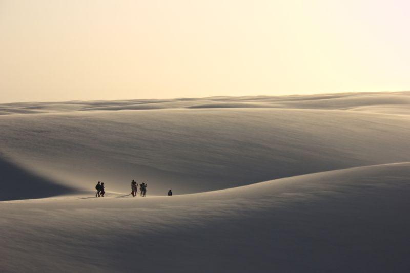 People at desert against sky