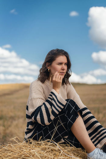 Beautiful young woman sitting on field against sky