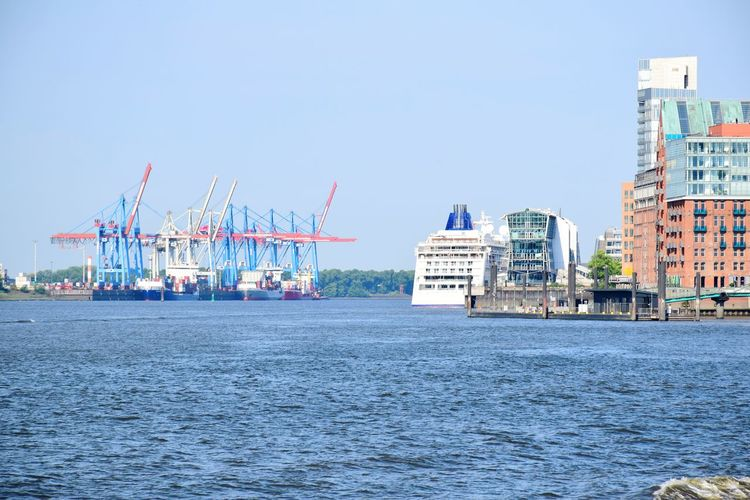 Cranes by sea against buildings in city against sky