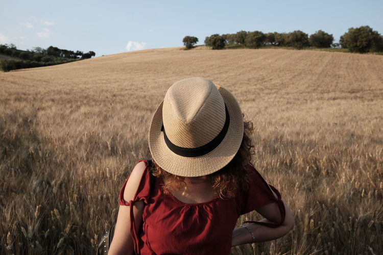 Woman with hat standing on field against sky