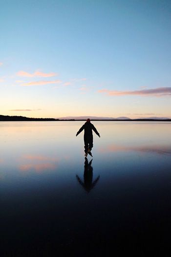 Man on lake against sky