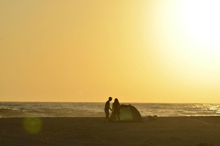 man and woman young couple in silhouette at dusk on ocean beach jointly working together to construct their camping tent for the evening in Baja California Sur, Mexico Beach Life Silhouettes Beach Beauty In Nature Communication Cooperation Couple - Relationship Couple Silhouette Dusk Horizon Horizon Over Water Joint Effort Land Leisure Activity Nature Ocean Beach Outdoors Real People Scenics - Nature Sea Sky Sunset Tent Tent Camping Two People Water Working Together Summer Sports