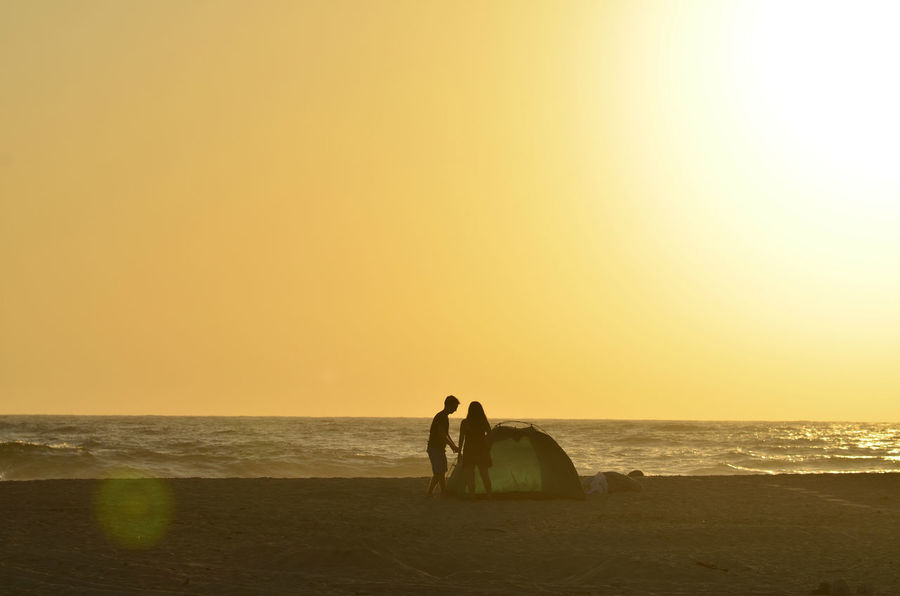 man and woman young couple in silhouette at dusk on ocean beach jointly working together to construct their camping tent for the evening in Baja California Sur, Mexico Beach Life Silhouettes Beach Beauty In Nature Communication Cooperation Couple - Relationship Couple Silhouette Dusk Horizon Horizon Over Water Joint Effort Land Leisure Activity Nature Ocean Beach Outdoors Real People Scenics - Nature Sea Sky Sunset Tent Tent Camping Two People Water Working Together
