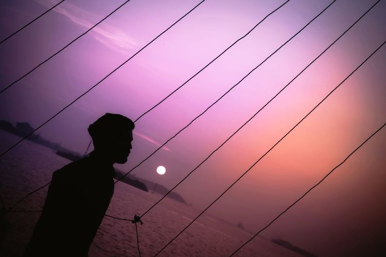 Silhouette person standing against sky during sunset
